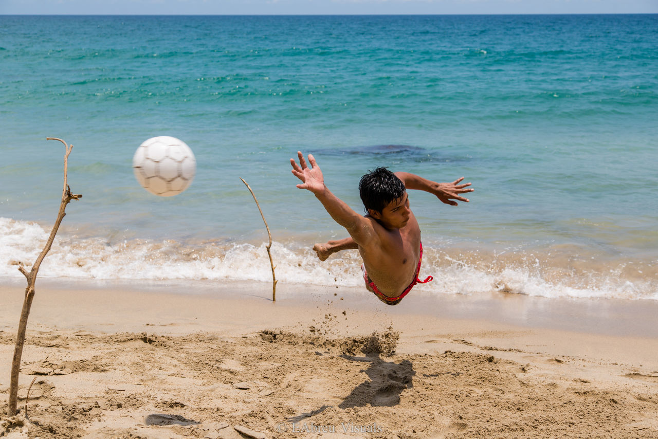 beach, sand, sea, ball, fun, shore, motion, playing, sport, leisure activity, one person, soccer ball, real people, soccer, football, mid-air, vacations, day, shirtless, outdoors, water, lifestyles, young adult, full length, men, nature, wave, sportsman, people