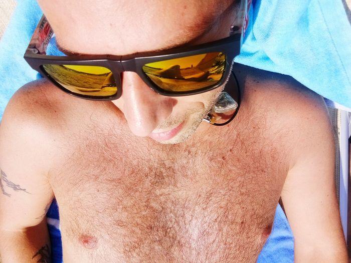 Close-up of shirtless man wearing sunglasses