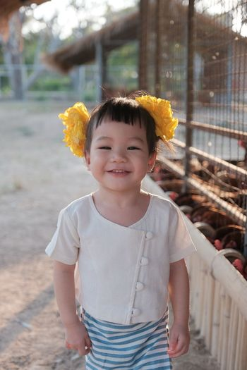 Portrait of cute smiling baby girl wearing yellow flowers while standing on footpath