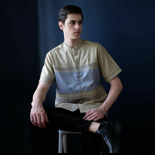 Portrait of young man sitting against black background