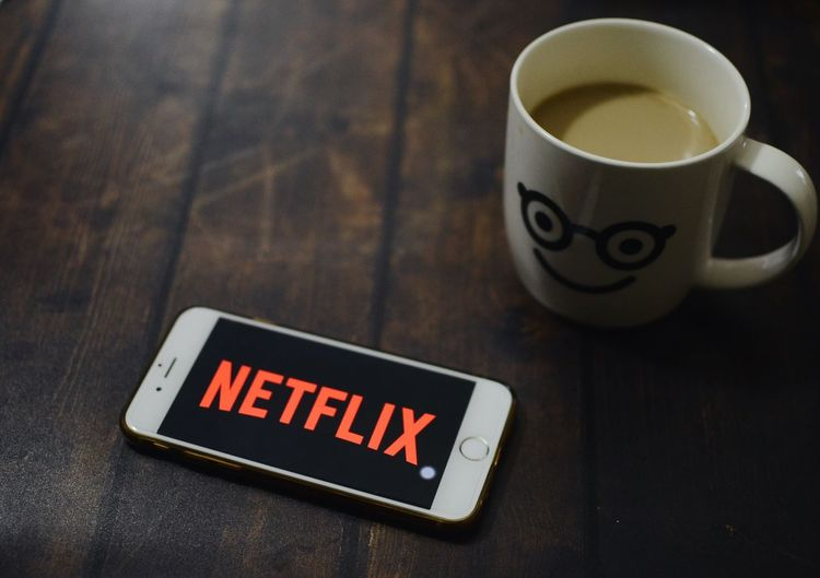 Netflix apps showing on iPhone 6 with a cup of hot coffee on wooden table . IPhone Netflix Cup Mug Food And Drink Text Drink Communication Western Script Coffee Cup Table No People Refreshment High Angle View Indoors  Coffee Close-up Coffee - Drink Focus On Foreground Still Life Food Technology