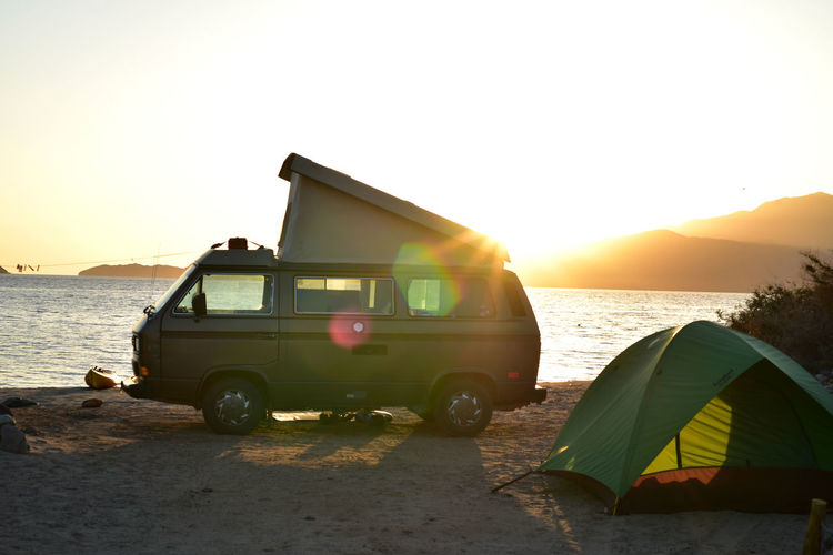 Pop-up camper van and tent silhouetted against sunrise sky in baja, mexico