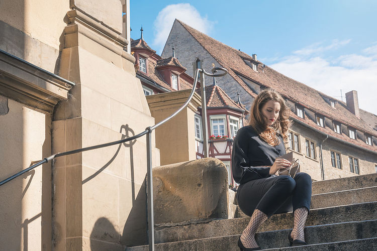 Young woman sitting on steps against sky