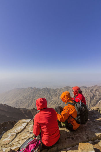 Rear view of people looking at mountain against sky