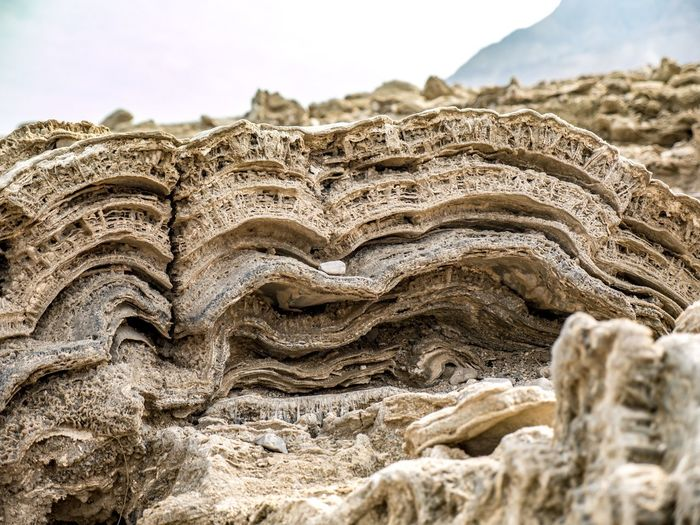 Close-up of rock formation on beach against sky