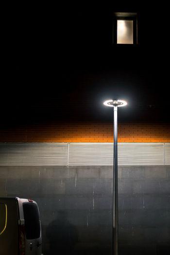 Illuminated street light against wall in city