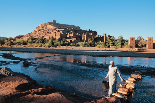 A berber carrying water from a river beside the kasbah of Aït Ben Haddou. Aït Benhaddou Been There. Desert Life Moroccan Morocco MoroccoTrip Connected By Travel National Geographic Riverside African Beauty Architecture Berber  Building Exterior Built Structure Clear Sky Full Length Historic Kasbah Maroc Nature Oasis Outdoors Real People Scenic View Water