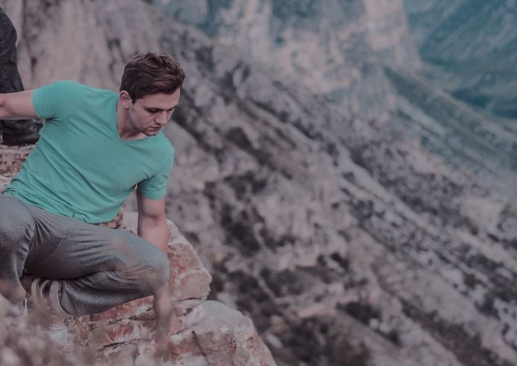 High angle view of man crouching on cliff