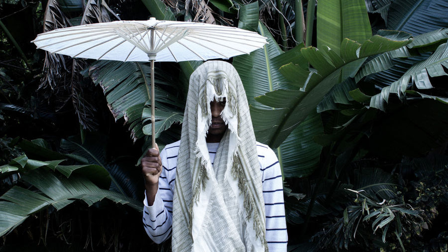 Man with white umbrella wearing scarf against banana tree