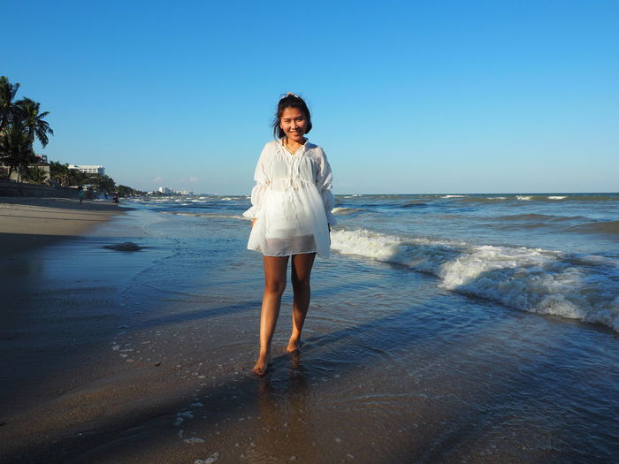Full length portrait of woman standing on beach against clear sky