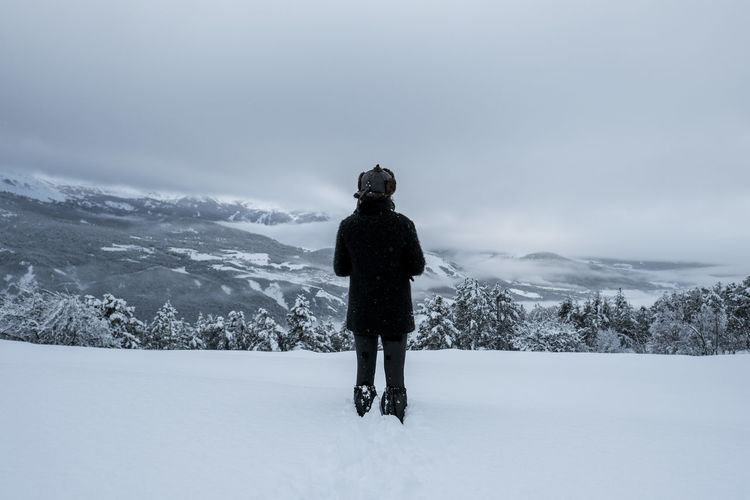 Rear view of person standing on snow field against sky