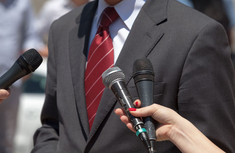 Cropped Hands Of People Holding Microphone By Businessman