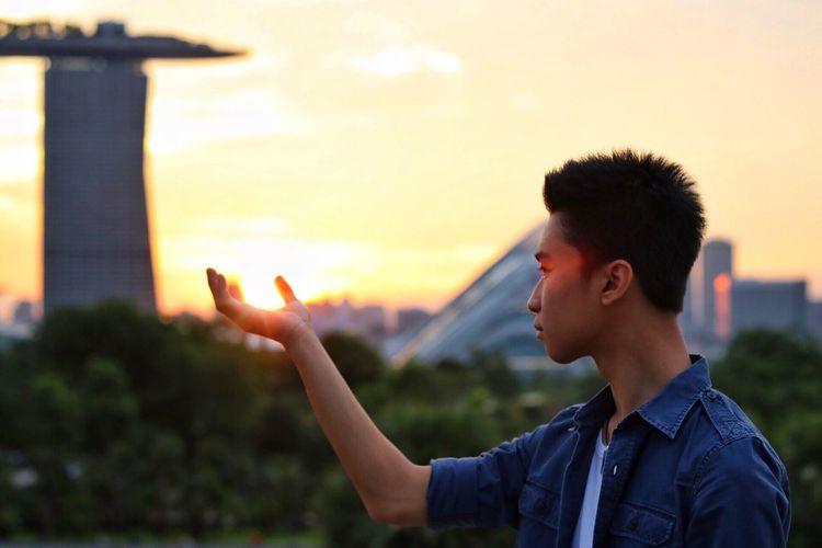 Optical Illusion Of Young Man Holding Sun At Marina Barrage