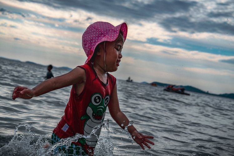 Girl wading in sea against sky during sunset