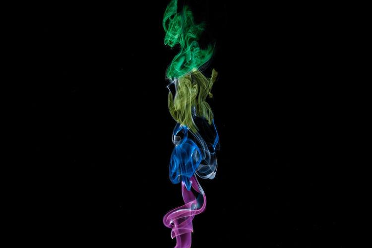 Close-up of multi colored illuminated smoke against black background