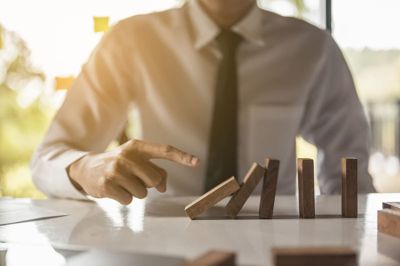 Midsection of businessman pushing dominoes on table