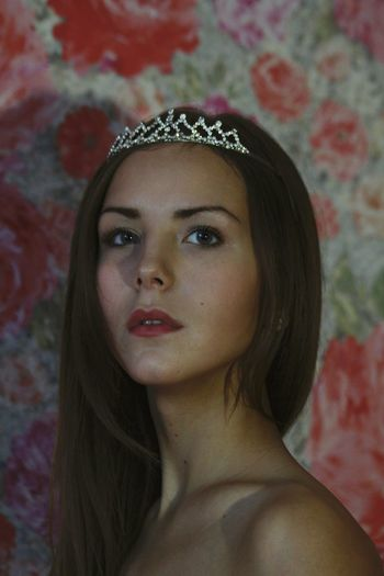 Close-up of beautiful woman wearing tiara against floral wallpaper