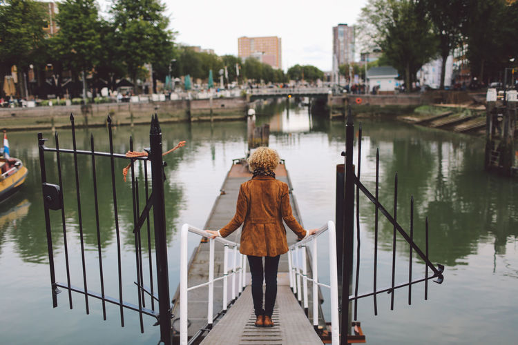 Rear view of woman standing on footpath leading towards pier at river