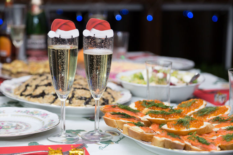 Close-Up Of Champagne Flutes With Santa Hats On Table