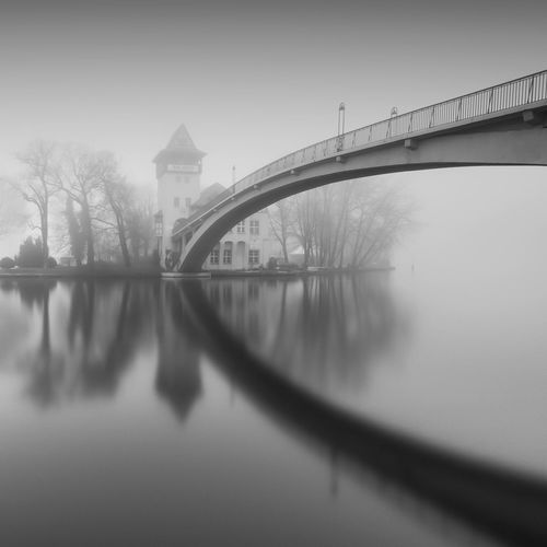 Isle of Youth   Berlin (2017) Reflection Bridge - Man Made Structure Water Built Structure Connection Architecture River Foggy Day Tranquil Scene Foggy Berlin Germany Tranquility Longexpoelite EyeEm Best Shots EyeEm Best Shots - Black + White Outdoors Travel Destinations No People Bridge Day City Tree Nature Sky The Great Outdoors - 2017 EyeEm Awards Black And White Friday Shades Of Winter