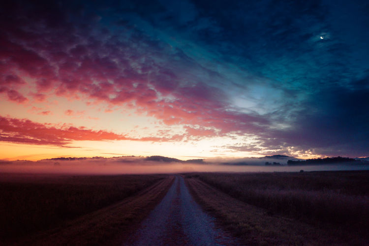 Empty Dirt Road On Field Against Sky During Sunset