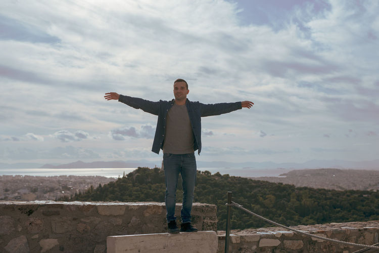 Man with arms outstretched standing on landscape against sky