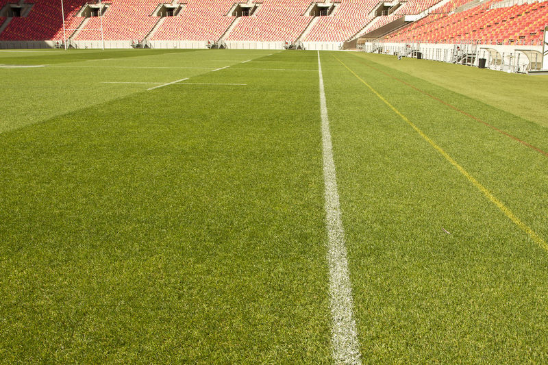 white touch line drawn on the grass of a sports stadium with empty red chairs in the background American Football - Sport American Football Field Competition Day Grass Green Color Match - Sport No People Outdoors Soccer Soccer Field Sport Stadium Yard Line - Sport