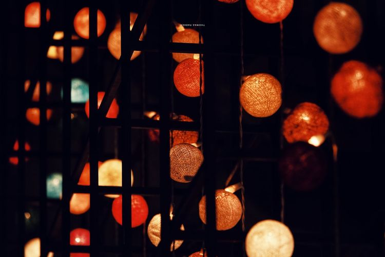 Low angle view of illuminated lights hanging at night