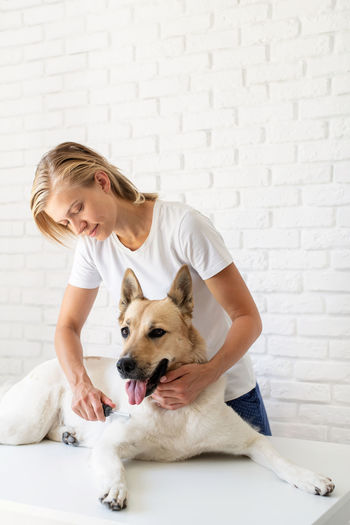 Woman with dog against wall