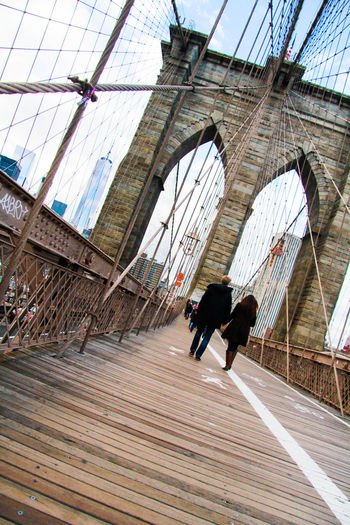 Tilt image of couple walking on brooklyn bridge