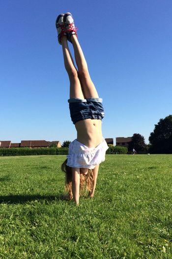 Full Length Of Girl Doing Handstand On Grassy Field Against Clear Blue Sky