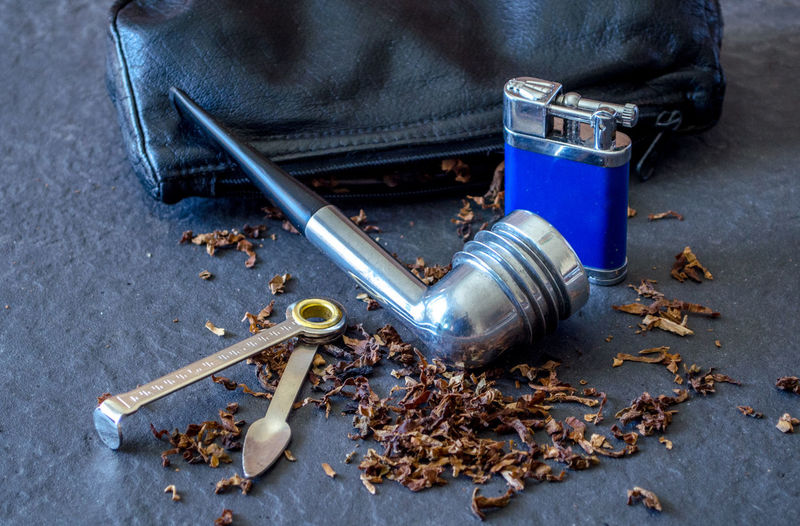 Close-Up Of Smoking Pipe By Cigarette Lighter Amidst Tobacco
