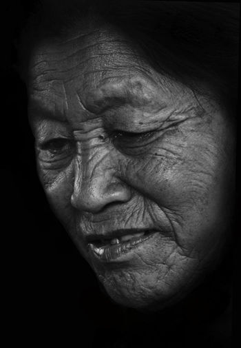 Close-Up Of Senior Woman Against Black Background