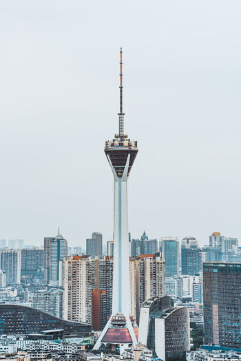Communications tower in city against clear sky
