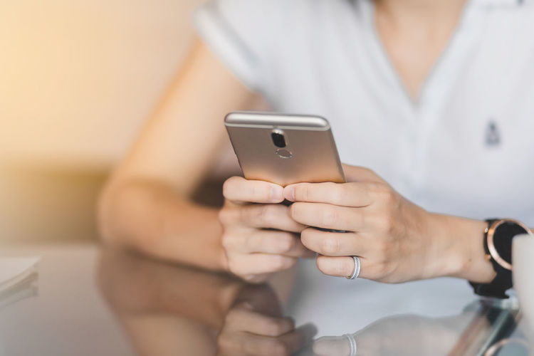 Adult Business Finance And Industry Communication Connection Focus On Foreground Front View Hand Holding Human Hand Indoors  Lifestyles Marketing Midsection Mobile Phone One Person Portable Information Device Smart Phone Technology Telephone Text Messaging Using Phone Wireless Technology Women