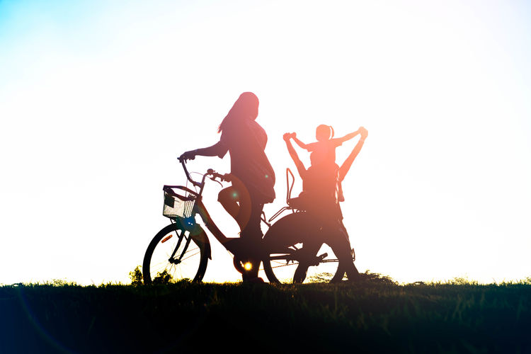 Silhouette people riding bicycle on field against clear sky
