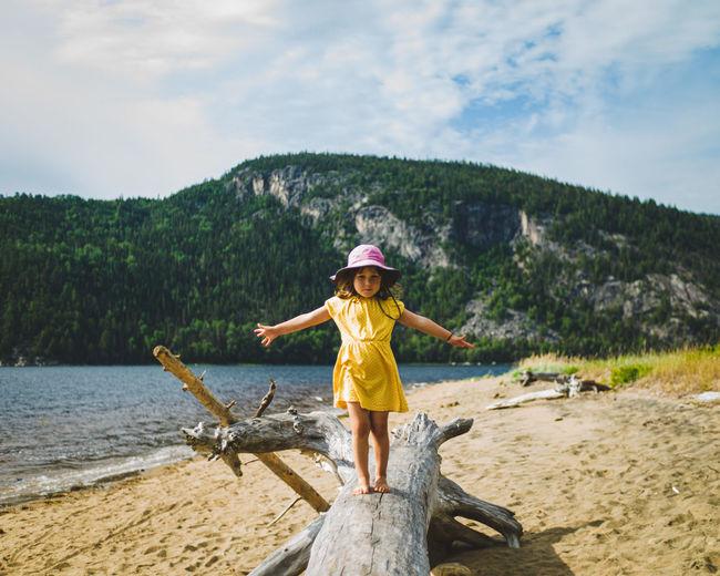 Full length of girl standing at beach against sky