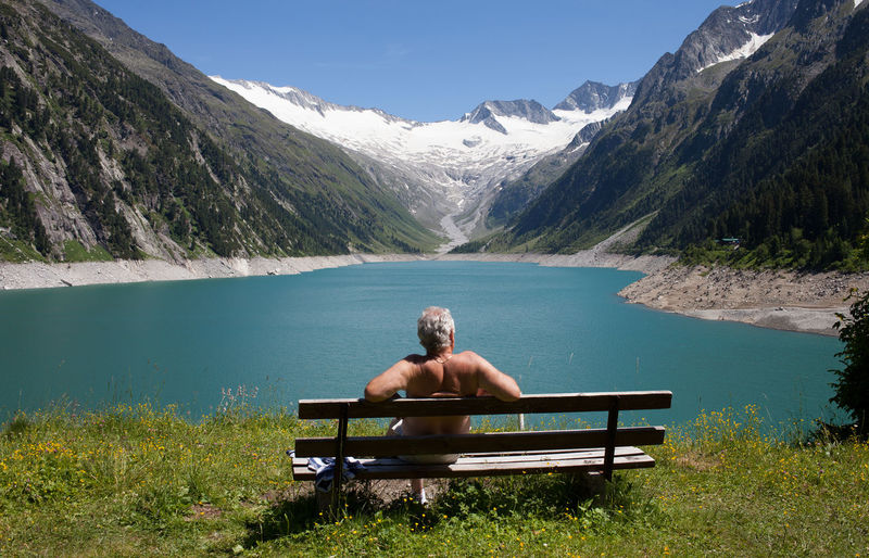 Portrait Of Man Sitting On Lake By Mountain Against Sky