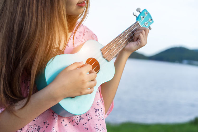 Midsection of woman playing ukulele against lake