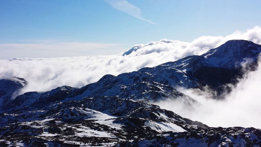 Scenic View Of Clouds Covering Snowcapped Mountains