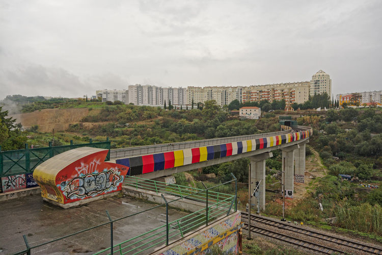 Colourfull train track with graffiti through urban wasteland with new apartment blocks in the background, lisbon, portugal Apartment Buildings Suburban Landscape Train Tracks Colorful Grey Sky Lisbon Portugaloteuolhar Suburban Suburban Exploration Suburbia