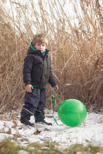Boy holding balloons in winter