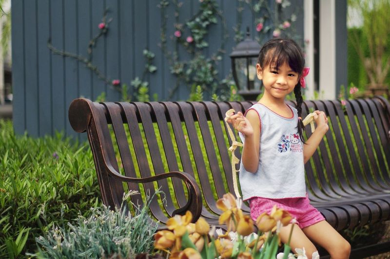 Portrait of smiling girl standing by plants
