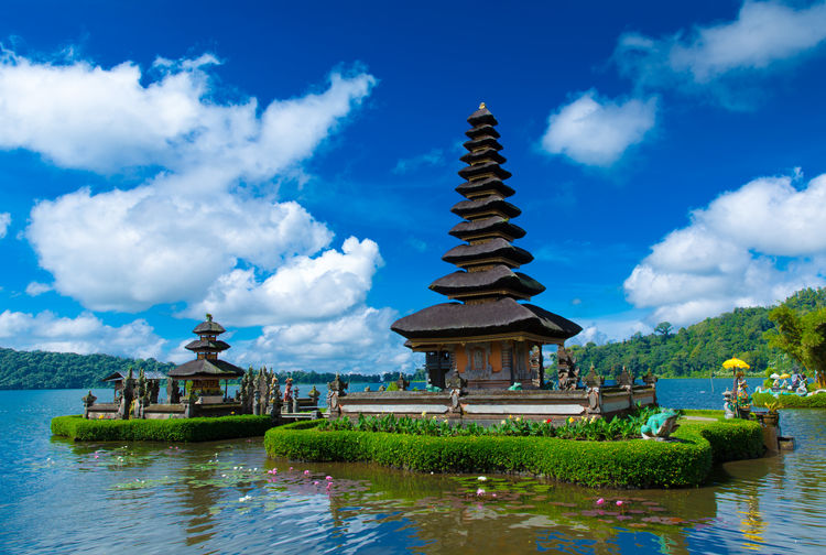 Scenic view of temple in river against cloudy sky