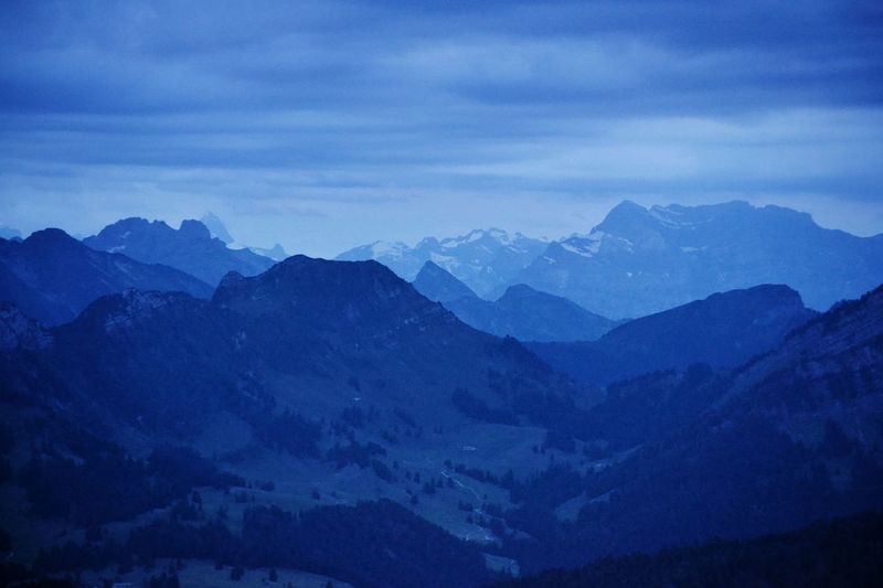 Scenic view of mountains against sky at dusk