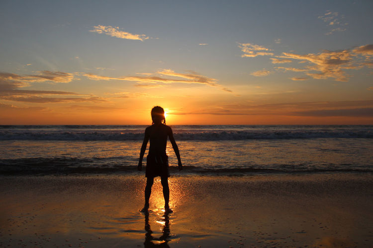 Boy standing at beach against sky during sunset