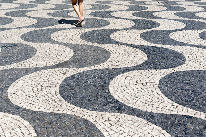 Surface of traditional cobble stone pavement in lisbon, portugal. person walking on footpath