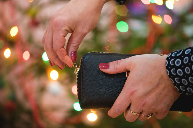 Cropped Hands Of Woman Opening Purse Illuminated Christmas Tree