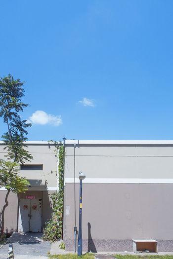 谁家一间小屋,紧闭两扇大门,门前一棵小树,房顶一朵白云。 cloud Sky Blue City Sunny Tree Building Door