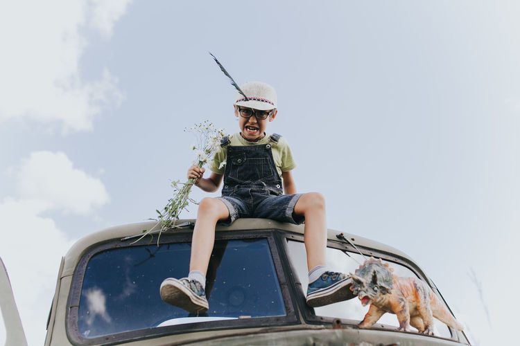 Low angle view of boy sitting on van against sky